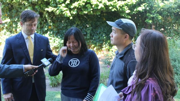 A tearful Huan Hua Kuang speaks with reporters about the death of her 6-year-old daughter Sofia Liu, who was killed by an UberX driver. Kuang, flanked by attorney Chris Dolan (left), and her husband, Ang Jiang Liu (center right), was advocating for stronger insurance requirements on smartphone ride booking companies like Uber Technologies that enable regular people to drive for hire using their own vehicles.