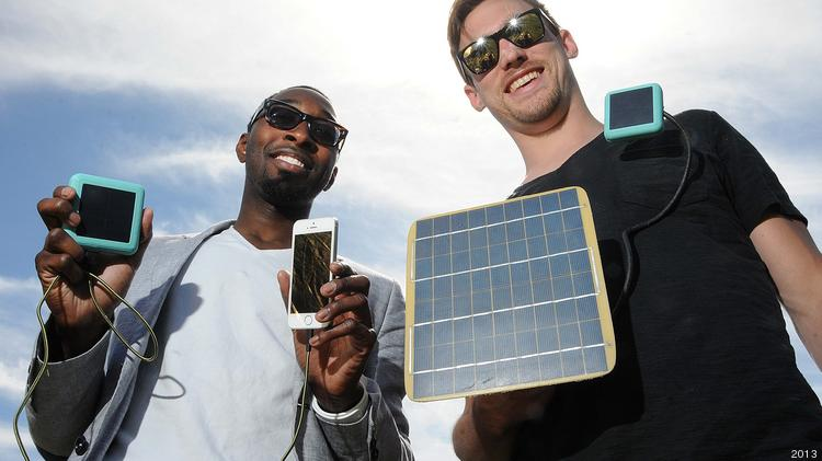 David Hunt (left) and Jason Browne , co-founders of Spor. Hunt has the SPOR charger (blue box) connected to a phone by USB cable, to either recharge or supply power. Browne has a solar panel connected by a gooseneck USB cable to a SPOR charger for recharging the Spor.