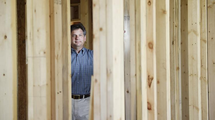 "Perry Cadman, general manager of Brookfield Residential of Colorado, with beetle-killed wood used in new home construction. He says, ""What we use is harvested and milled in Colorado and that means jobs, Colorado jobs."""