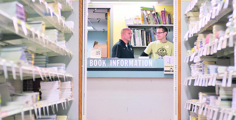 Chris Gotski, associate director at the University of Colorado Book Store, talks with Eric Schissler, sales assistant in the textbook section of the store.
