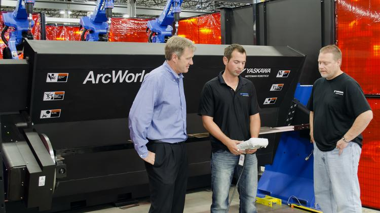 (Left) Steve Barhorst, president and chief operating officer of Motoman Robotics talks with employees.