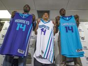 Charlotte Hornets draft picks P.J. Hairston (left), Noah Vonleh (right) and General Manager Rich Cho (center) show off the team's fresh new uniforms, revealed last week, at a press conference to introduce the team's two new players.