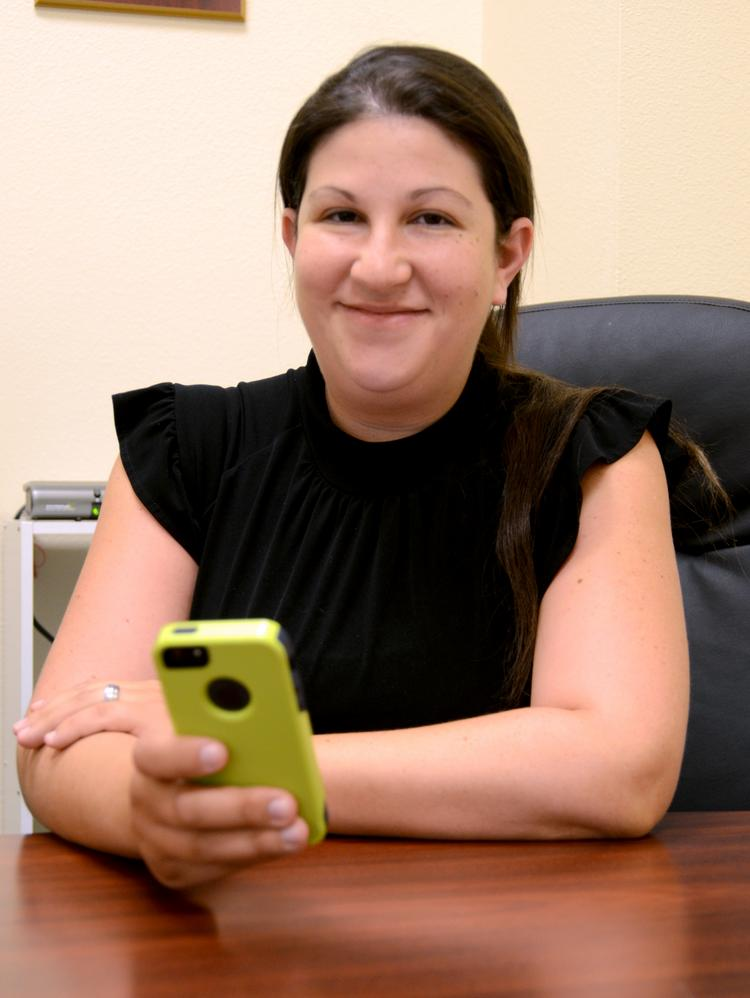 Jessica Reyna in the Collis Roofing Inc offices with her smart phone.