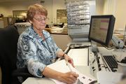 Carolyn Jones, counting assistant for Wright Flood, processes clients and insured checks.
