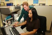Connie O'Brien, cash manager, speaks with Tara Johnson, senior clerk, in the finance department of Wright Flood.