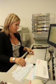 Brittany White, counting assistant for Wright Flood, processes clients and insured checks.