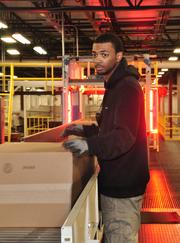 Jamair Coleman, a package handler, checks boxes before they go through an automated scanner. Coleman is one of 208 employees, up from 170 when the distribution center opened last August.