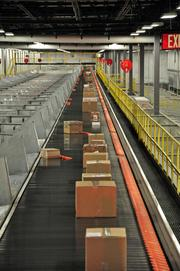 The orange devices on one side of the conveyor belt, called shoes, rapidly push packages down one of 52 chutes that correspond with a delivery route.