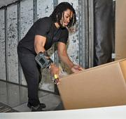 """Shane Moore uses a """"ring scanner"""" before loading packages onto a 28-foot-long trailer. Each trailer can fit about 1,000 packages and take an hour to load."""