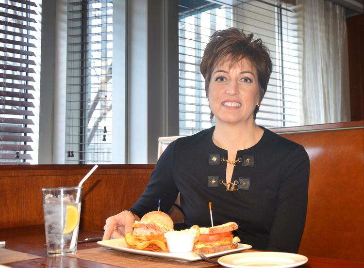 Marie Milie Jones, founding partner of JonesPassodelis PLLC, gets ready to dig into halves of her favorite sandwiches — grilled Arctic char and Yeungling beer-battered Atlantic cod — at the Original Fish Market.