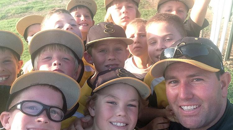 40 Under 40 honoree Justin Kasel with the Little Shockers 8-year-old baseball team he's coaching this summer.