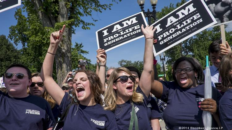 Activists who oppose the Affordable Care Act's mandate for employers to provide contraceptive coverage celebrate outside the U.S. Supreme Court after the court's ruling in the Hobby Lobby case.