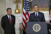 """Representative Mel Watt, a Democrat from North Carolina and U.S. President Barack Obama's nominee as director of the Federal Housing Finance Agency (FHFA), left, and Thomas """"Tom"""" Wheeler, managing director of Core Capital Partners LP and Obama's nominee as chairman of the Federal Communications Commission (FCC), right, listen as Obama makes an announcement in the State Dining Room of the White House in Washington, D.C., U.S. on Wednesday, May 1, 2013. Obama nominated Watt to be director of the Federal Housing Finance Agency after months of political pressure from consumer advocates to find a new overseer for Fannie Mae and Freddie Mac."""
