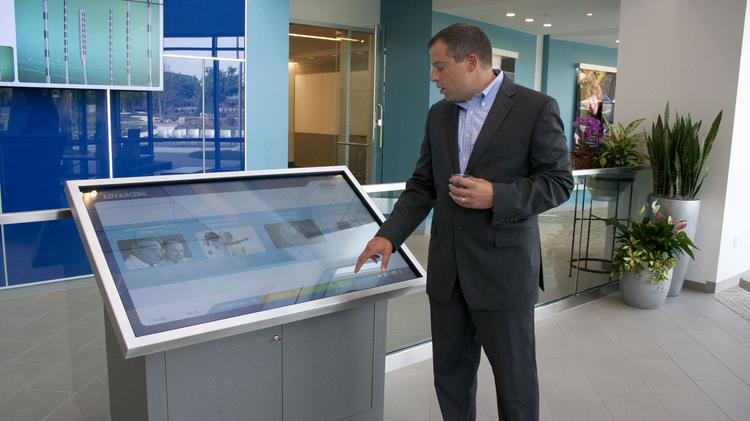 Paul Donhauser, Boston Scientific's director of global facilities operations and real estate, shows off interactive displays in the lobby of the new Boston Scientific building in Marlborough.