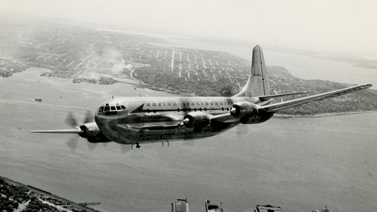 Decades ago, a Boeing Stratocruiser flies over Seattle on an overcast day.