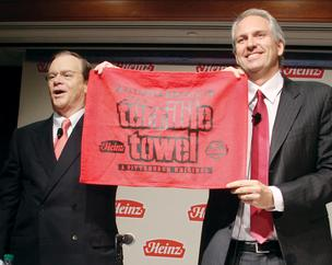 H.J. Heinz Company Chairman and President William Johnson, left, and 3G Capital Managing Partner Alex Behring hoist a Heinz special edition of a Terrible Towel during a news conference Thursday, in which it was announced that Heinz has entered into a definitive merger agreement to be acquired by an investment consortium comprised of Berkshire Hathaway and 3G Capital.
