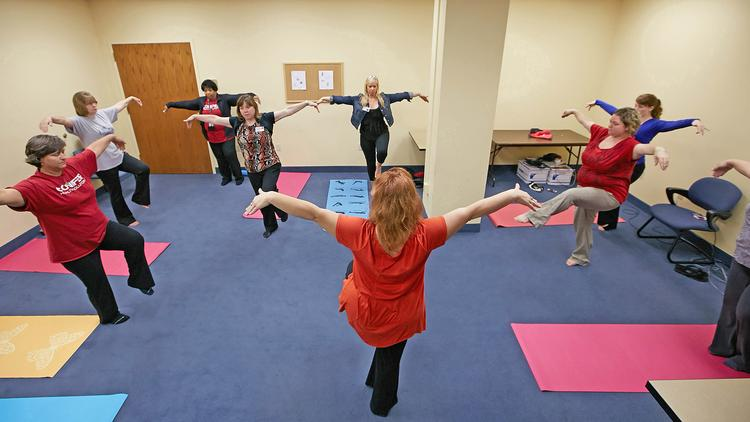 KentuckyOne Health Inc. employees participate in a yoga class during Wellness Wednesday. The company, the winner in the 15,000+ employees category in Business First's 2013 Healthiest Employers of Greater Louisville awards program, works hard to promote employee wellness.