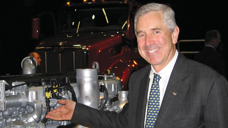 Mark Pigott, patriarch of the Pigott family, gestures toward a new Paccar engine.