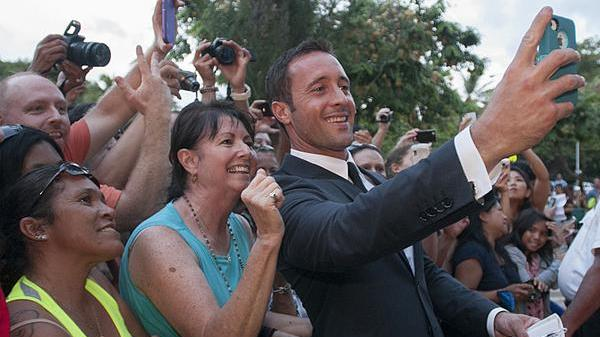 "Actor Alex O'Loughlin, who plays Steve McGarrett on the CBS drama ""Hawaii Five-0,"" takes a picture with a fan at the show's fourth season premiere at Sunset on the Beach in Waikiki in this 2013 file photo. The event drew thousands of people, who got to see a free concert by the Jonas Brothers before screening the show's premiere episode a night before its broadcast debut. The show's fifth season will premiere at Sunset on the Beach this year on Sept. 13."