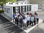 A five-container half-megawatt UniEnergy battery system, with a group of employees. A state grant announced Tuesday for utilities will help several local counties purchase the battery systems to store energy for later use.