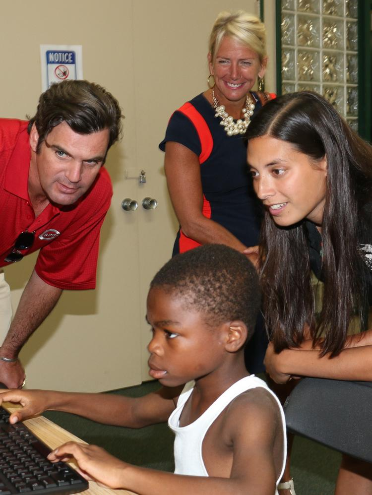 From left, Cincinnati Reds COO Phil Castellini, Procter & Gamble vice president of brand for North America Jodi Allen, and Sofia Cifuentes of the Cincinnati Zoo talk with kids in the computer room at the Millvale Community Center.