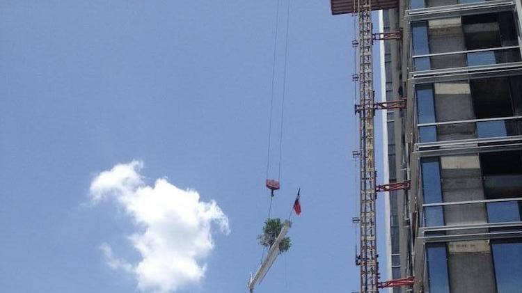 A steel beam is hoisted from the ground to the top of the 30-story Colorado Tower. The building's topping off ceremony was held on July 3. Click on the photo to see several images from the event.