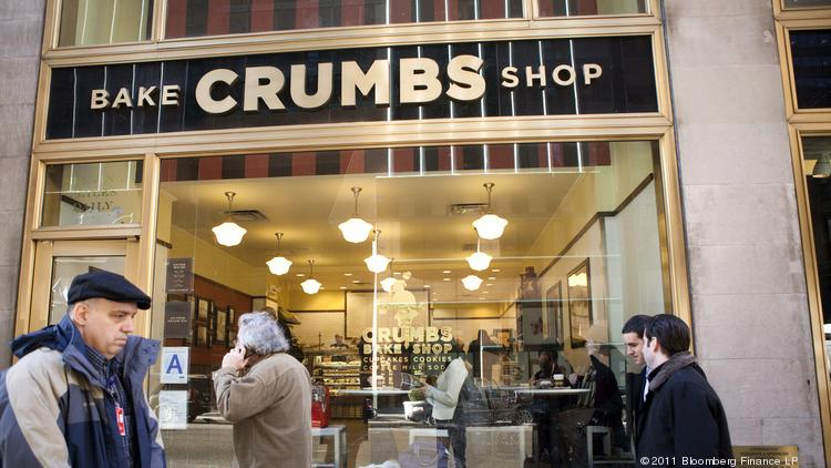 Pedestrians walk past a Crumbs cupcake store in New York.