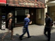 Pedestrians pass by a closed Crumbs Bake Shop Inc. store in New York, U.S., on Tuesday, July 8, 2014. Crumbs Bake Shop Inc., the cupcake chain facing default on more than $14 million in loans, closed all of its stores yesterday after years of struggling to make money in a crowded market. Photographer: Peter Foley/Bloomberg