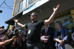 James Lathrop, owner of Cannabis City, the first retail marijuana shop set to open in Seattle, declares to the crowd gathered outside his store