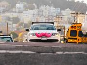 Lyft cars can be identified by the pink mustache on the front.