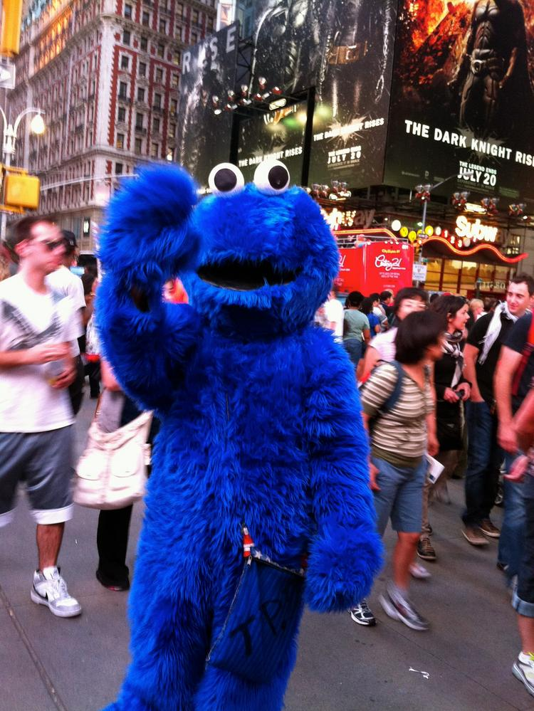 A person dressed as Cookie Monster seeks tips for posing in photographs in Times Square.