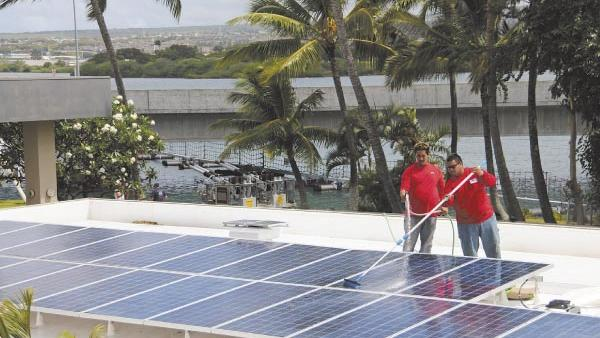 Workers install PV panels on the roof of a business in Hawaii in this file photo. HECO is planning to level the playing field when it comes to rooftop solar.