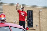 U of L point guard Peyton Siva waves to the crowd from atop a fire truck.