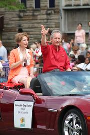 Mayor Greg Fischer shows his support for the University of Louisville Cardinals as he rides along the parade route with wife Dr. Alexandra Gerassimides.