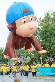 "A ""Curious George"" balloon, handled by ZirMed Inc. employees, makes its way down Broadway."