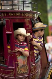 Little cowboys in a stagecoach watched the crowds who watched them.