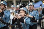 A marching band member plays the horn during the parade.