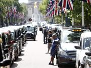 Ridesharing companies are seen as a threat by traditional taxi services: Here, in a photo from June, London taxi drivers use their smartphones as they stand alongside their parked cabs near Buckingham Palace, during a protest against Uber Technologies Inc.'s car sharing service . Traffic snarled in parts of Madrid and Paris that day, with a total of more than 30,000 taxi and limo drivers from London to Berlin blocking tourist centers and shopping districts. Photographer: Simon Dawson/Bloomberg