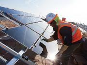 A worker installs panels made by First Solar at a power plant in Arizona. The Tempe company has announced its first project in Chile.