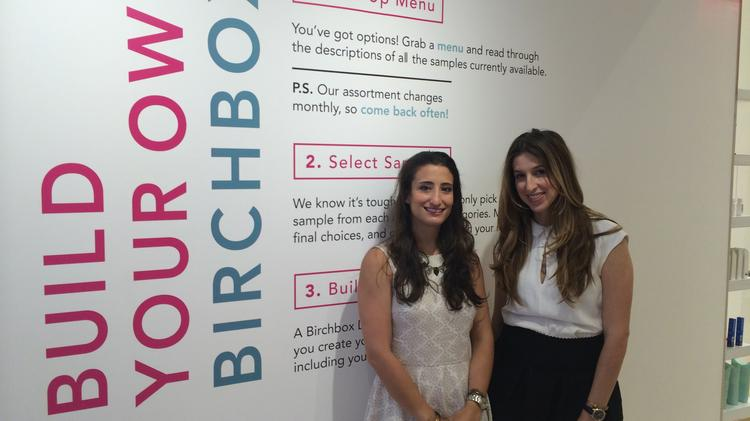 """Hayley Barna, left, and Katia Beauchamp, Birchbox's co-founders, stand at the beginning stage of the store's """"Build Your Own Birchbox"""" beauty sampling/discovery zone."""