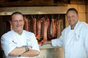 Executive Chef Ryan Terry and boyhood friend & Holy Cross classmate Tom Secrist, pit master, pose inside the smokehouse, where the ribs pick up that smoky flavor. The smokehouse sits off the parking lot from the restaurant.