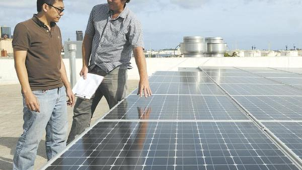 Eric Carlson, right, a partner with Honolulu-based RevoluSun, said that the company is in talks with big battery energy storage firms to bring in this type of technology to Hawaii. [PBN file].