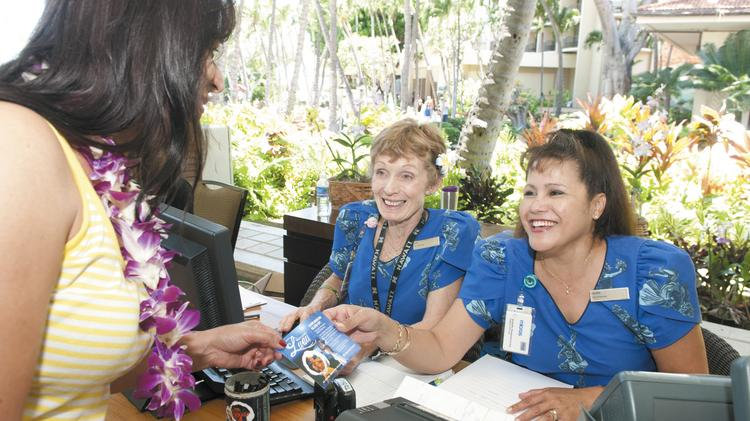 Hilton Hawaiian Village food and beverage cashiers Lisa Wong, center, and Laurie Canencia provide details of a luau to a visitor to the hotel. Hilton Hotels Hawaii Region is one of the largest nongovernment employers in Hawaii, according to PBN research.