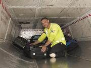 Michael Nascimento, ramp agent and belt loader, helps to unload the luggage that is stored on the fuselage of a Hawaiian Airlines plane.