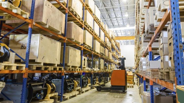 A large warehouse and distribution center with forklifts.