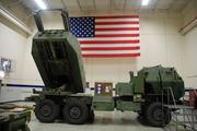 An American flag flies above the front of a HIMARS Multiple Launch Rocket System vehicle in a bay at Lockheed Martin Missiles and Fire Control's Grand Prairie plant.