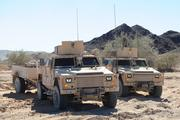 Two of Lockheed Martin's Joint Light Tactical Vehicles are tested in a desert terrain.