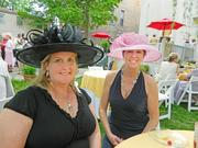 Friends Jarita Stephens, left, and Maria Eckerle tried on hats that were on display (and for sale) at the Old Louisville garden party on Thursday.