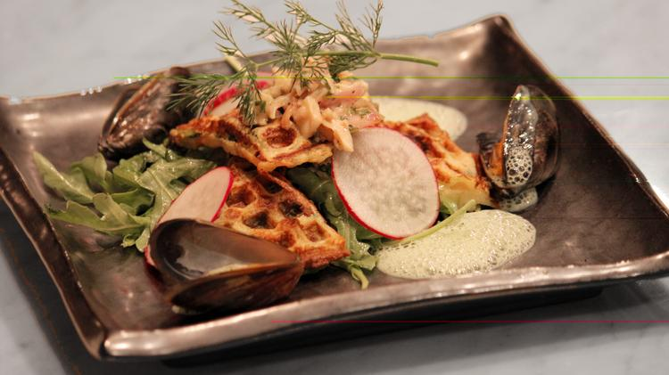 Mosselwafel met kreeft dish, which is a waffle stuffed with dill, mussels and lobster meat sitting on a bed of baby arugula and thin sliced radishes topped with a lobster tartar and garnish with a sprig of dill and a parsley foam. Bistro BE opens in Miami on July 18.
