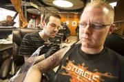 Waukesha Tattoo's Jason Vogt works on client Jack Straehler.Click here for story.